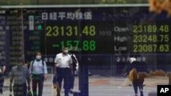 Orang-orang menunggu di persimpangan lalu lintas, tercermin pada monitor yang menunjukkan indeks Nikkei 225 Jepang di sebuah perusahaan sekuritas di Tokyo pada hari Senin, 17 Agustus 2020. (Foto: AP)