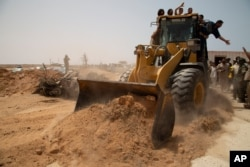 A bulldozer pushes earth to during a ceremony to reopen the road between the Libya cities of Misrata and Sirte, June 20, 2021. It was later reported closed.