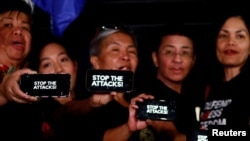 """FILE - Journalists, including Rappler CEO Maria Ressa, raise their smart phones with words """"STOP THE ATTACKS!"""" in a rally for press freedom in Quezon City, Philippines, Feb. 15, 2019."""