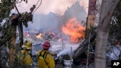 Firefighters try to extinguish the flames at a burning house as the South Fire burns in Lytle creek, San Bernardino County north of Rialto, Calif., Aug. 25, 2021.
