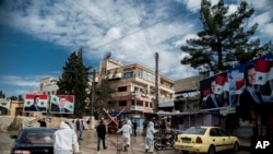 FILE - In this March 24, 2020, file photo, workers spray disinfectant to prevent the spread of the coronavirus on a street lined with billboards showing Syrian President Bashar Assad, in Qamishli, Syria.