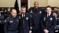 In this July 27, 2021 photo, from left, U.S. Capitol Police Sgt. Aquilino Gonell, Washington Metro Police Dept. officer Michael Fanone, U.S. Capitol Police Sgt. Harry Dunn and Washington Metro Police Dept. officer Daniel Hodges pose after a House hearing.