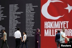 FILE - The names of civilians and police killed while resisting a failed coup attempt are displayed on a banner in Taksim Square, Istanbul, Turkey, July 20, 2016. The slogan reads: 'Sovereignty belongs to the nation.'