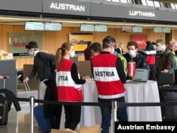 Austrians heading home get their papers checked on March 23, 2020 at Dulles Airport.