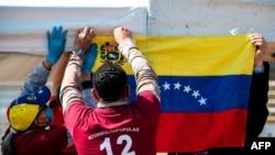 """Migrantes venezolanos cuelgan una bandera nacional durante una """"consulta popular"""" convocada por el líder de la oposición venezolana Juan Guaidó en Bogotá, el 12 de diciembre de 2020."""