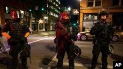 Policías de armados con fusiles de guerra mantienen la vigilancia en Portland, Oregon, durante protestas en agosto.