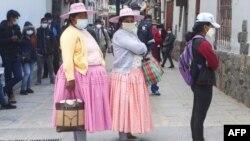 Mujeres peruanas usan barbijo mientras hacen fila frente a un banco en Puno, Perú, el 5 de octubre de 2020.