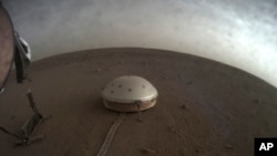 This April 25, 2019 photo made available by NASA shows the InSight lander's dome-covered seismometer on Mars. On Oct. 1, 2019, scientists released an audio sampling of marsquakes and other sounds recorded by the probe.