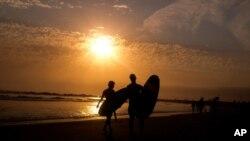 加州洛杉磯威尼斯海灘夕陽下的衝浪者。(2021年6月16日)