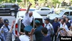 FILE - Azerbaijani journalist Afgan Mukhtarli greets supporters as he is taken to court in Baku, Azerbaijan, May 31, 2017.