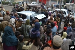Daily wage workers, jobless due to coronavirus outbreak, rush to a car to receive free food distributed in Quetta, Pakistan, March 23, 2020.