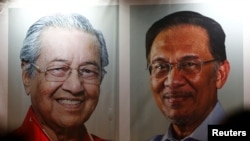 FILE - People pass posters of Malaysian Prime Minister Mahathir Mohammad and politician Anwar Ibrahim, who was granted a royal pardon, at a rally in Kuala Lumpur, Malaysia, May 16, 2018.