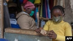 FILE - A fabrics trader and her child wear face masks to guard against the new coronavirus in her shop inside Lilongwe City market in Lilongwe, Malawi, May 18, 2020.