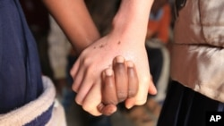 Mina Godfrey, right, holds hands with her friend Charity Kamwendo at her school in this May, 24, 2016 photo taken in Machinga, north east of Blantyre Malawi.