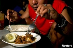 A customer eats dog meat in Yogyakarta May 28, 2011. A meal comprising of dog meat and plain rice costs about 8000 rupiah ($0.90).