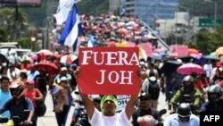 En la foto de archivo del 6 de agosto de 2019, cientos de personas participan en una protesta para exigir la renuncia del presidente hondureño, Juan Orlando Hernández, por sus presuntos vínculos con el narcotráfico, en Tegucigalpa.