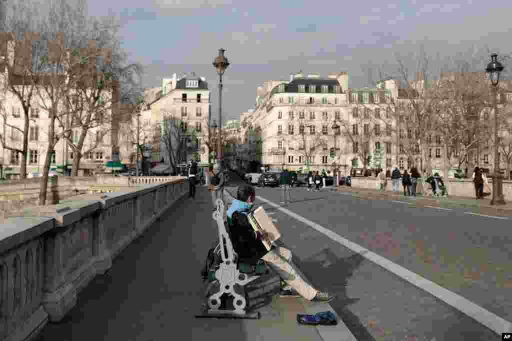 در این روز آفتابی در پاریس مردی روی پلی مشغول نواختن آکاردئون است. همهگیری کرونا در فرانسه همچنان بالا است. هفتاد در صد بخش مراقبتهای ویژه مراکز درمانی پر هستند.