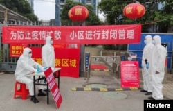 FILE - Workers in protective suits are seen at a checkpoint for registration and body temperature measurement, at an entrance to a residential compound in Wuhan, Hubei province, China, Feb. 13, 2020.