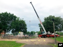 A heavy crane that will be used to help dig up the remains of former Confederate Gen. Nathan Bedford Forrest sits at a park in Memphis, Tenn., June 1, 2021.