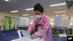 A woman wearing a face mask to help protect against the spread of the new coronavirus casts a vote for the parliamentary elections at a polling station in Seoul, South Korea, Wednesday, April 15, 2020. South Korean voters wore masks and moved slowly…