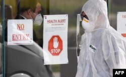 A medical worker enters the Epping Gardens aged care facility in the Melbourne suburb of Epping on July 30, 2020, as the city battles fresh outbreaks of the COVID-19 coronavirus.