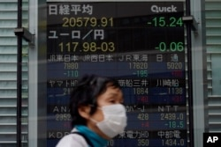 A masked woman walks past an electronic stock board showing Japan's Nikkei 225 index at a securities firm in Tokyo, May 21, 2020.