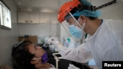 FILE - A nurse gets a swab from a man under observation for coronavirus disease (COVID-19) in a booth set up in a hospital parking lot in Manila, Philippines, April 15, 2020.