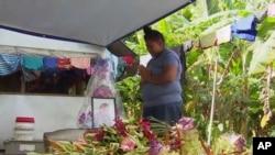 Dalam gambar dari video ini, seorang wanita berdoa di depan potret anaknya yang tewas karena campak di Apia, Samoa. Samoa menutup semua sekolahnya, 18 November 2019, dan mengamanatkan agar semua orang mendapat vaksinasi. (Foto: AP)