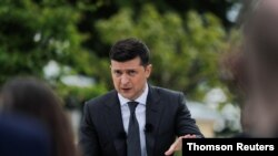 Ukrainian President Volodymyr Zelenskiy gestures during an open-air news conference, one year after his inauguration, amid the outbreak of the coronavirus disease in Kyiv, May 20, 2020.