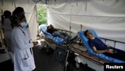 Trabajadores de la salud observan a las personas después de recibir una dosis de la vacuna contra la enfermedad por coronavirus en un centro de vacunación en San Salvador, el 13 de julio de 2021.
