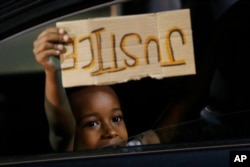 A young boy holds a 'Justice' sign as he peers outside the window of a car passing protesters marching through downtown for a third night of unrest May 31, 2020, in Richmond, Va.