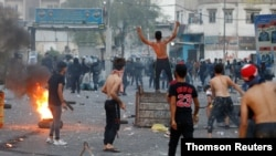 Iraqi demonstrators clash with Iraqi security forces during a protest over poor public services in Baghdad