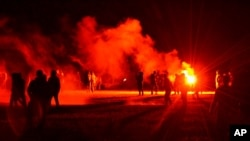 Sejumlah anak muda berkumpul di sebuah lapangan saat bentrok dengan polisi yang membubarkan pesta disko ilegal di Redon, Brittany, Perancis, Jumat, 18 Juni 2021.