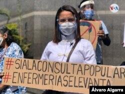 Una trabajadora del sector salud en Venezuela sostiene un cartel que muestra su acuerdo con la consulta popular en ese país. Foto Álvaro Algarra/VOA.