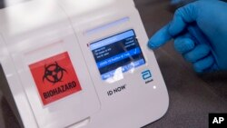 FILE - A scientist runs a mock COVID-19 sample test in Washington, D.C., April 28, 2020.