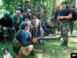 Juru bicara Abu Sayyaf Abu Sabaya, di latar depan, terlihat bersama kelompok ekstremis bersenjata. Pasukan Filipina menangkap seorang komandan pemberontak Abu Sayyaf yang disalahkan atas penculikan uang tebusan selama bertahun-tahun dan pada hari Minggu, 21 Maret 2021. (Foto: AP)