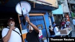 Voluntarios utilizan un megáfono cerca de un centro de votación para la consulta popular destinada a rechazar las elecciones parlamentarias del 6 de diciembre en el barrio de bajos ingresos de La Cruz en Caracas. Diciembre 12, 2020.