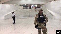 This still image provided by WABC-TV shows law enforcement standing in front of a New York City Subway entrance at the Oculus transportation hub after reports of a suspicious package on a subway platform in New York on Aug. 16, 2019.