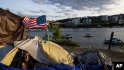 FILE - Frank, a homeless man, sits in his tent with a river view in Portland, Ore., on June 5, 2021.