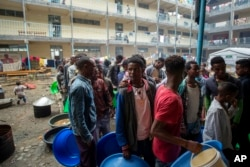 FILE - Displaced Tigrayans queue to receive food at the Hadnet General Secondary School, which has become a makeshift home to thousands displaced by the conflict, in Mekelle, in the Tigray region of northern Ethiopia, May 5, 2021.