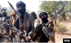 """Members of a """"bandit"""" gang pose with weapons at their forest hideout in northwestern Zamfara state, Nigeria, Feb. 22, 2021. (Sani Malumfashi/VOA)"""