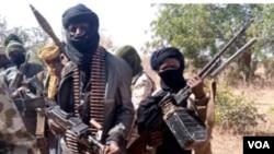 """Des membres d'un gang de """"bandits"""" avec des armes dans leur cachette dans la forêt du nord-ouest de l'État de Zamfara, au Nigéria, le 22 février 2021."""