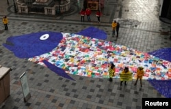 Some 800 shopping bags made of plastic sewed together in the shape of a fish are laid out by environmental activist group Greenpeace, in a protest against the pollution of oceans by plastic, in a street in Vienna.