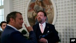 FILE - Conservative radio host Sebastian Gorka, right, speaks with White House correspondent for Playboy magazine Brian Karem, after President Donald Trump spoke about the 2020 census in the Rose Garden of the White House, in Washington, July 11, 2019.