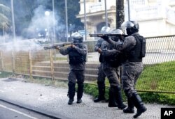 Military police fire the shotguns at demonstrators during a protest against crimes committed by the police against black people in the favelas, outside the Rio de Janeiro's state government, Brazil, Sunday, May 31, 2020.