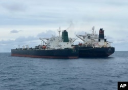 Kapal tanker MT Horse berbendera Iran (kiri) dan kapal tanker MT Frea berbendera Panama terlihat berlabuh bersama di perairan Pontianak, lepas pulau Kalimantan, Minggu, 24 Januari 2021. (Dalam foto yang dirilis oleh Badan Keamanan Maritim Indonesia (BAKAMLA via AP)