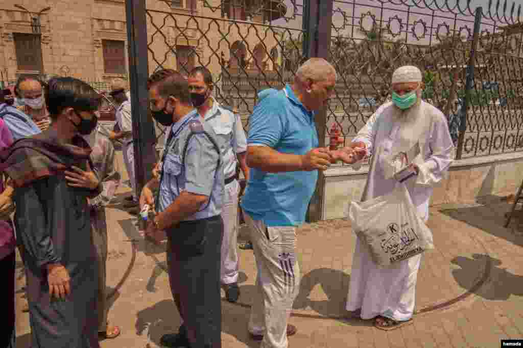 A man distributes prayer rugs and masks outside Al-Azhar Mosque in Cairo, Aug. 28, 2020. (Hamada Elrasam/VOA)