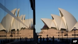 People walk around the waterfront of at Campbell Cove in Sydney, Australia, May 19, 2021.