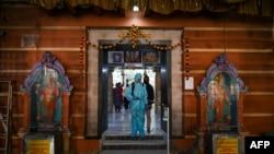 一名工作人員在孟買的一個印度教寺廟進行消毒,以避人們感染新冠病毒。圖片:2020年11月15日