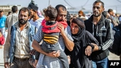 A man, suspected of having collaborated with the Islamic State group, is greetd by family members upon his release from the Kurdish-run Alaya prison in the northeastern Syrian city of Qamishli, on Oct. 15, 2020.